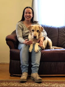 Kép: Egy mosolygós hölgy épp egy kanapén ülv és a vakvezetőkutyája az ölében fekszik.