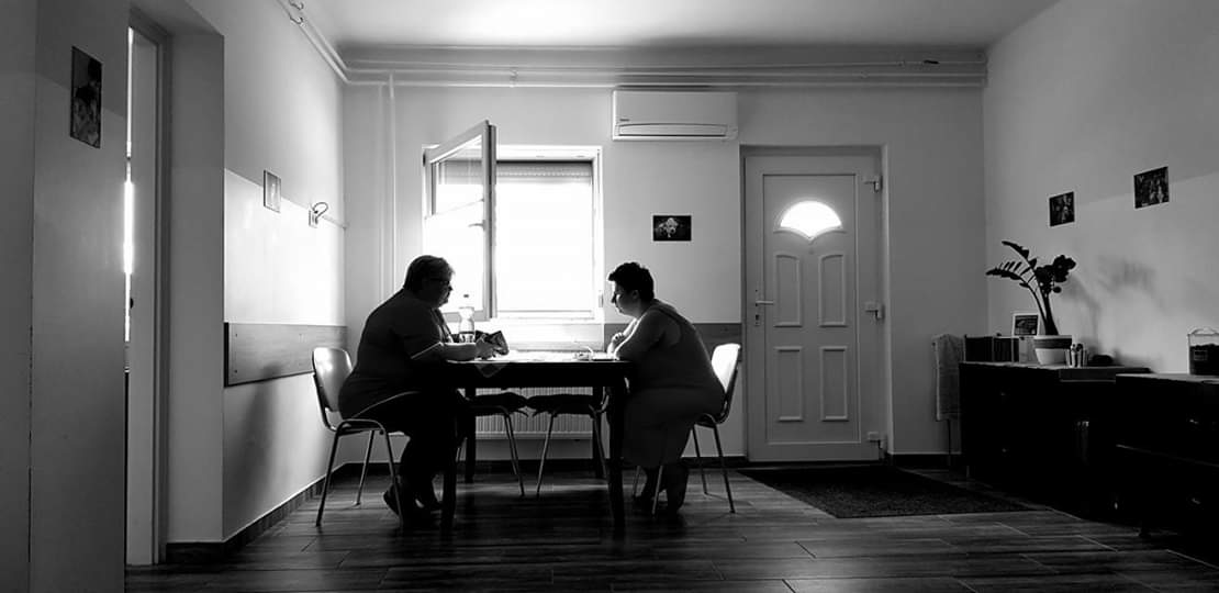 Fekete-fehér kép: A VKK központbna egy asztalnál ülő kiképző és egy hölgy épp az felékszítésről beszélgetnek