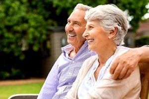 kép: egy idős űr és egy idős hölgy mosolyogva, átkarolva egymást ülnek egy padon