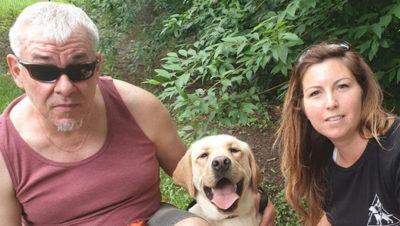 A képen Zoltán és Enikő között boldogan vigyorog Kökény, a sárga színű, labrador retriever vakvezetőkutya.