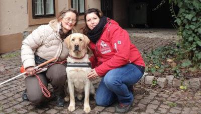 A képen Marica és Enikő között a gyönyörű Kökény vakvezetőkutya figyel.